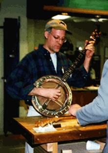Demonstrating a handcrafted banjo at a woodworking fair